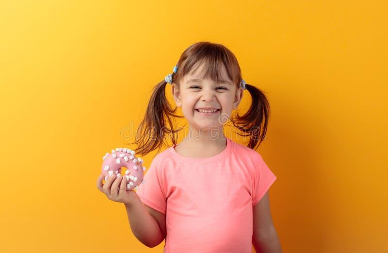Vierjähriges Mädchen in einem rosa T-Shirt essen Donut stockbilder