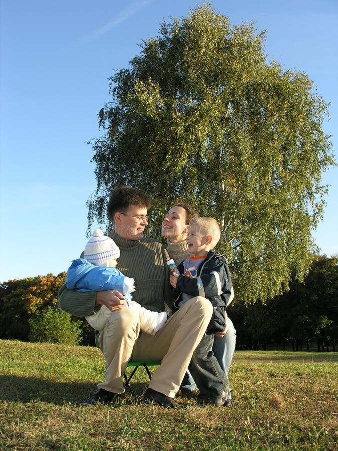 Vierköpfige Familie auf Herbst 3 des blauen Himmels des Grases stockfotos
