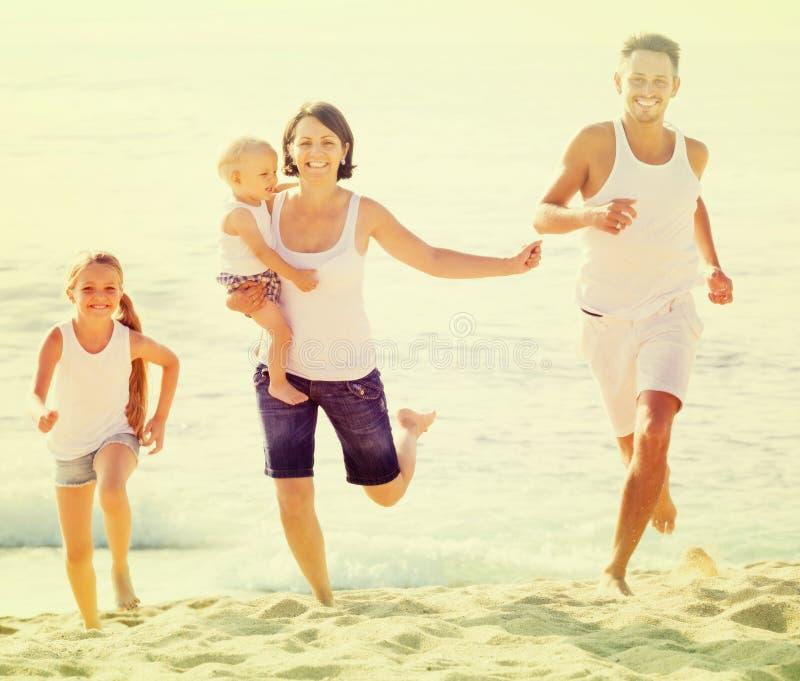 Vierköpfige Familie, die auf sandigem Strand auf sonnigem Wetter läuft lizenzfreies stockbild