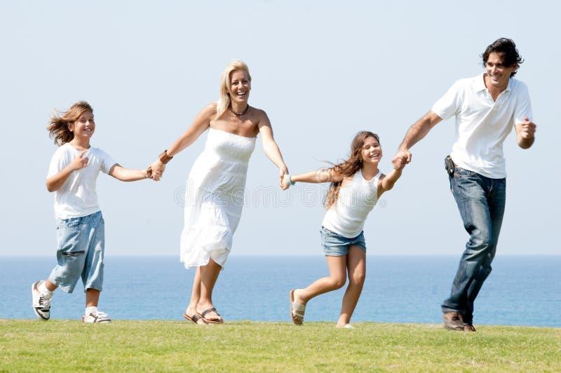 Vierköpfige Familie, die auf Wiese läuft stockbilder