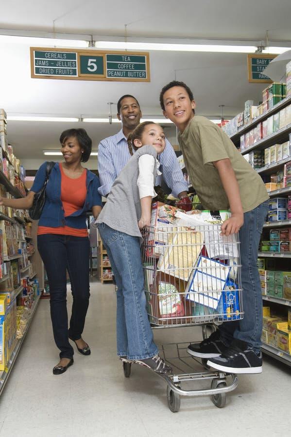 Vierköpfige Familie, die im Supermarkt kauft lizenzfreies stockbild