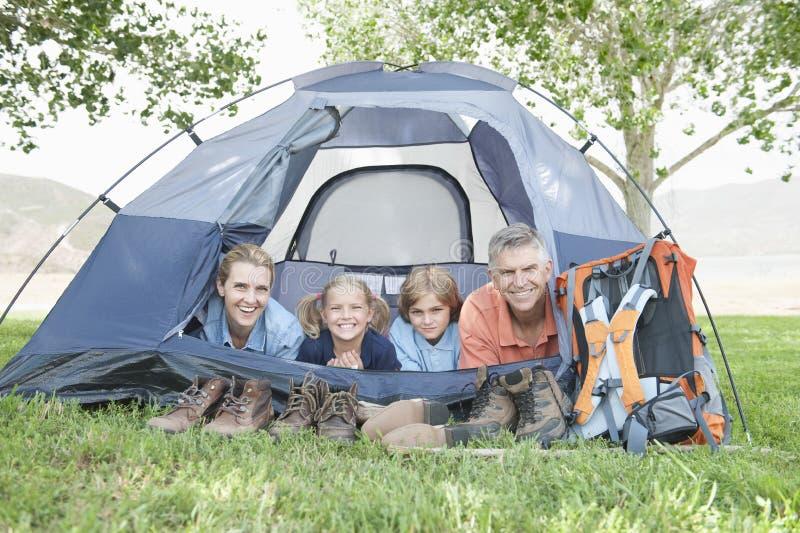 Vierköpfige Familie, die im Zelt lächelt lizenzfreie stockfotografie