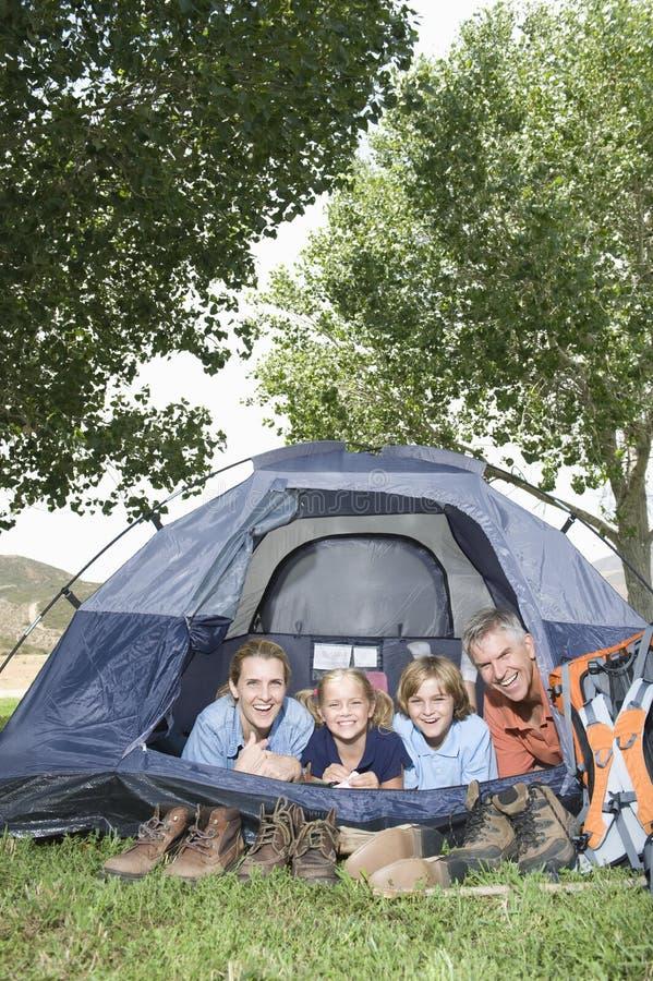 Vierköpfige Familie, die im Zelt lächelt lizenzfreie stockfotos