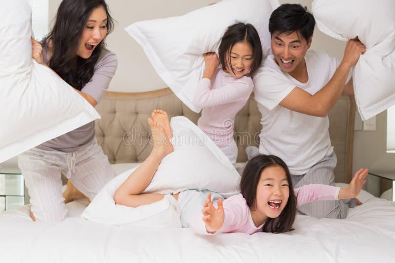 Vierköpfige Familie, die Kissenschlacht auf Bett hat stockfotos