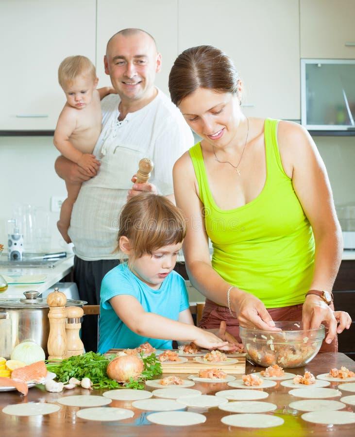 Vierköpfige Familie, die macht zusammen russische Mehlklöße (pelmeni) lizenzfreie stockbilder