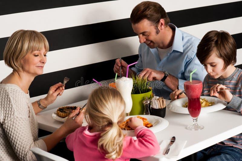 Vierköpfige Familie, die Mahlzeit im Restaurant hat stockfotografie