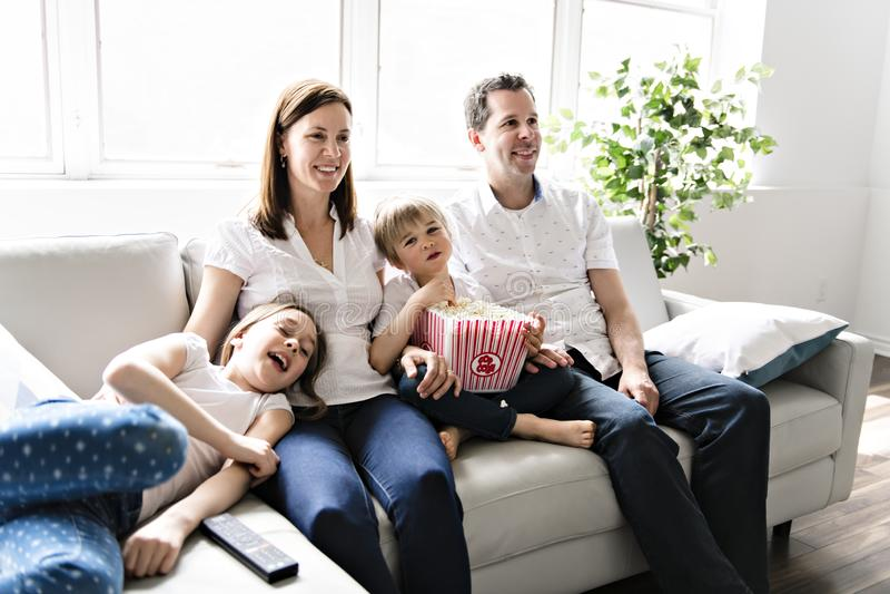 Vierköpfige Familie, die Spaß auf dem Sofa zu Hause aufpasst Film mit Popcorn hat stockfoto