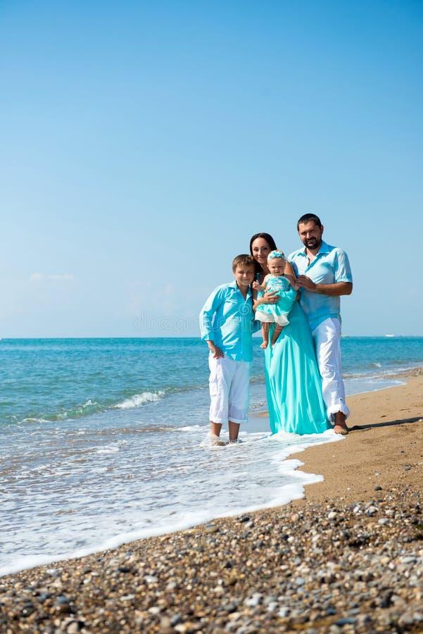 Vierköpfige Familie, die Spaß auf tropischem Strand hat stockfoto
