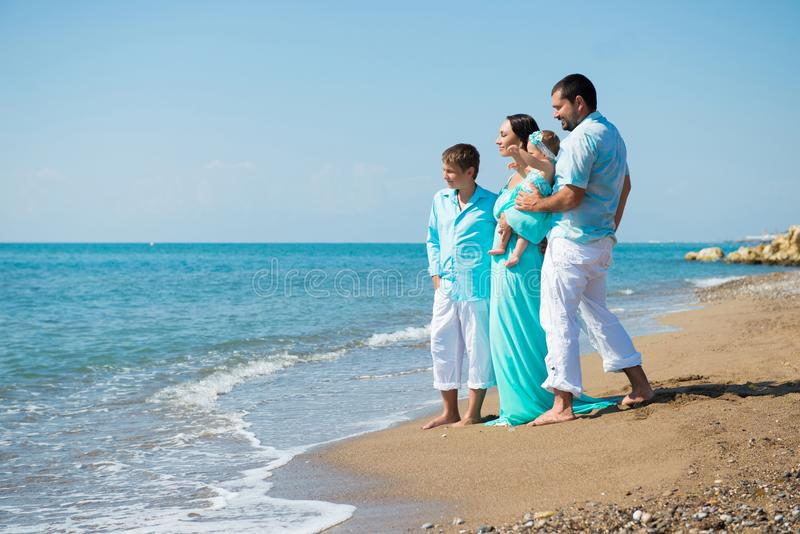 Vierköpfige Familie, die Spaß auf tropischem Strand hat lizenzfreie stockfotos