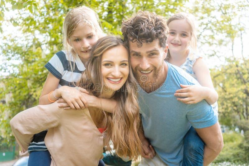 Vierköpfige Familie, die Spaß haben und Eltern, die das Kinderdoppelpol tragen lizenzfreies stockbild