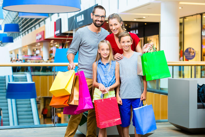Vierköpfige Familie im Einkaufszentrum mit Taschen stockbild