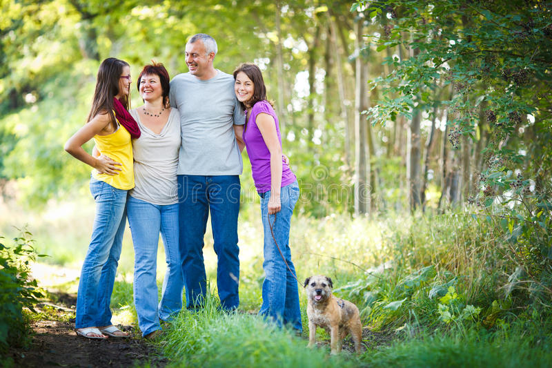 Vierköpfige Familie mit einem netten Hund draußen stockfotos
