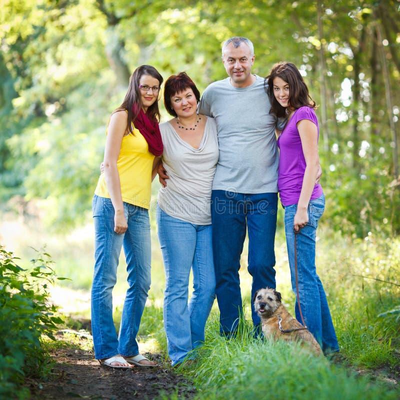 Vierköpfige Familie mit einem netten Hund draußen lizenzfreie stockfotografie