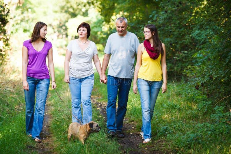 Vierköpfige Familie mit einem netten Hund draußen lizenzfreie stockfotos