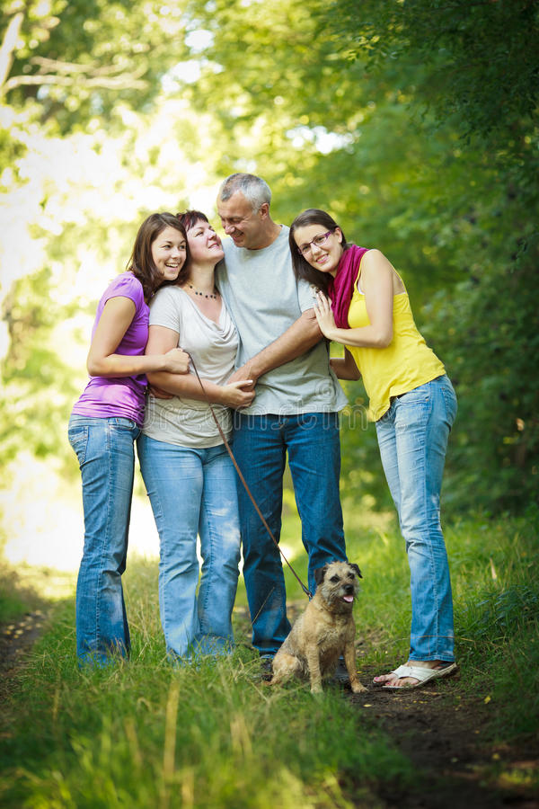 Vierköpfige Familie mit einem netten Hund draußen stockfotografie