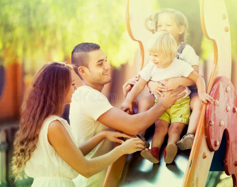 Vierköpfige Familie am Spielplatz stockbilder