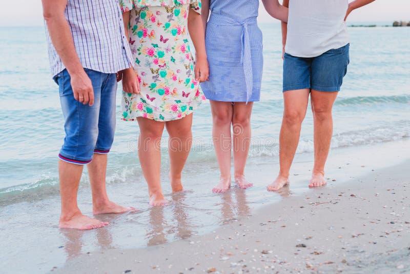 Vierköpfige Familie steht barfuß auf der Küste lizenzfreie stockfotos