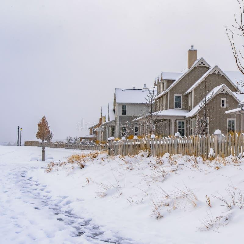 Vierkant die de Winterweer met sleep op de sneeuw naar de huizen in Dageraad wordt gestempeld royalty-vrije stock afbeeldingen