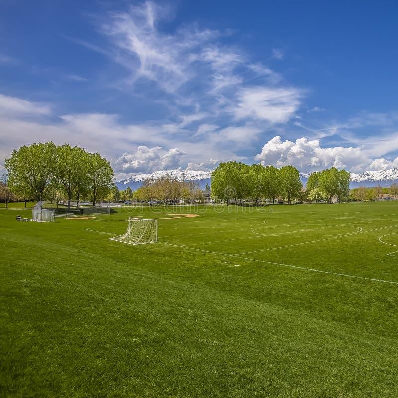 Vierkant Enorm sportterrein met netto voetbaldoel en honkbalbleachers achter een omheining stock foto's