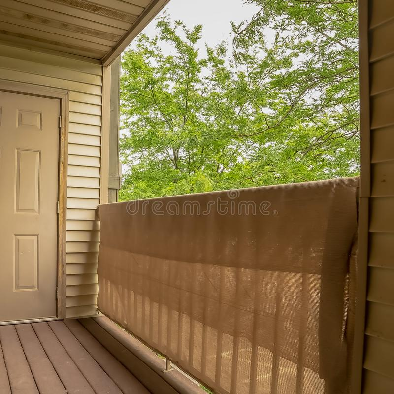 Vierkant frame Balcony of a home with white wall siding and view of bomen against white sky royalty-vrije stock foto's