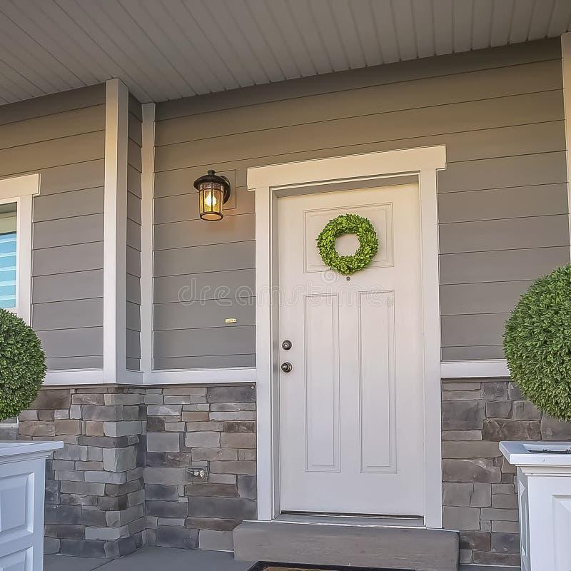 Vierkant Huis met kroon op de deur en een combinatie van hout en steenbakstenen muur stock afbeelding