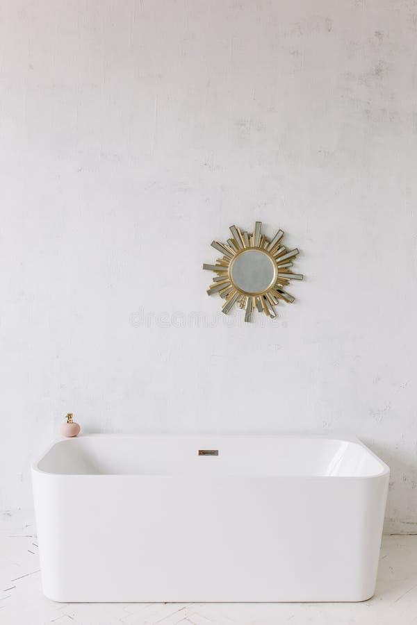 Vierkant kader van moderne badkamers met freestanding witte badkuip op achtergrond van de zolder de rustieke muur met de spiegel  stock afbeeldingen