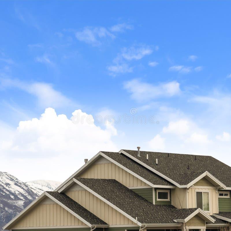 Vierkant kaderhuis buiten met mening van het donkere geworpen dak tegen een bewolkte blauwe hemel stock afbeelding