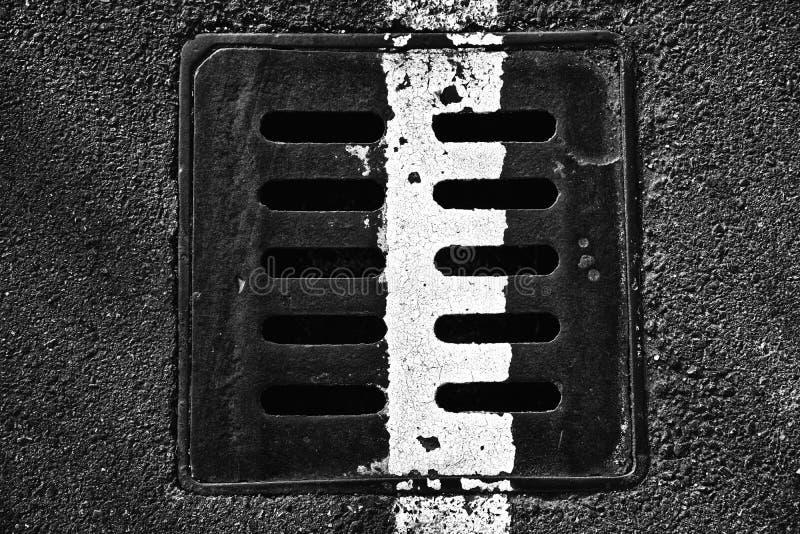 Vierkant metaalbroedsel in stedelijke bestrating, de dekking van het rioolmangat met m royalty-vrije stock fotografie