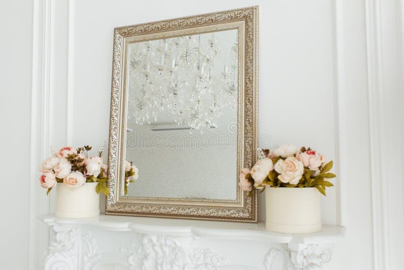 Vierkant uitstekend spiegelkader op de woonkamermuur over open haard met fotokader, en bloemenboeket royalty-vrije stock fotografie