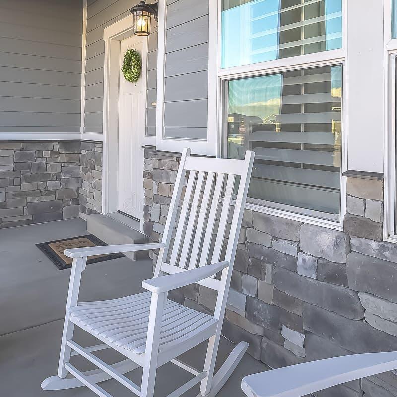 Vierkante die kaderportiek met schommelstoelen en deur met kroon bij de voorgevel van een huis wordt bekeken royalty-vrije stock foto