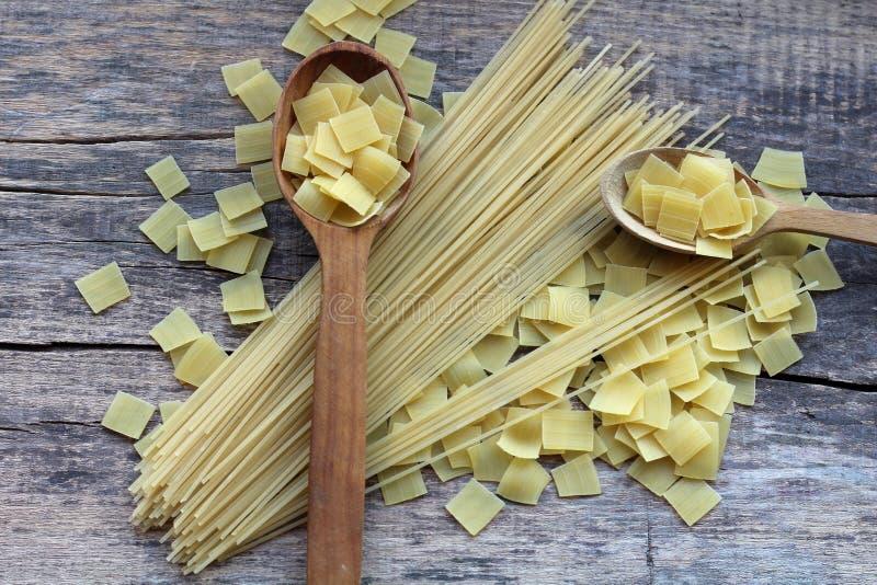 Vierkante droge gele deegwaren in een mengeling met lange spaghetti op en dichtbij de houten lepels royalty-vrije stock afbeeldingen