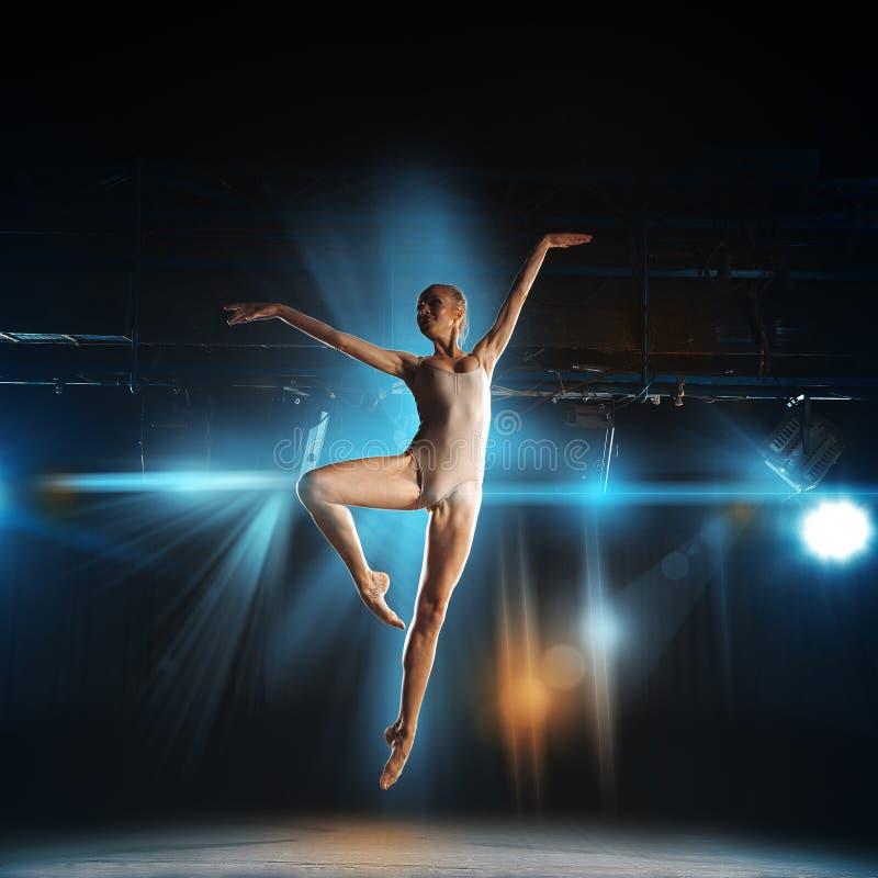 Vierkante foto van jonge blondeballetdanser in sprong op stadium royalty-vrije stock afbeeldingen