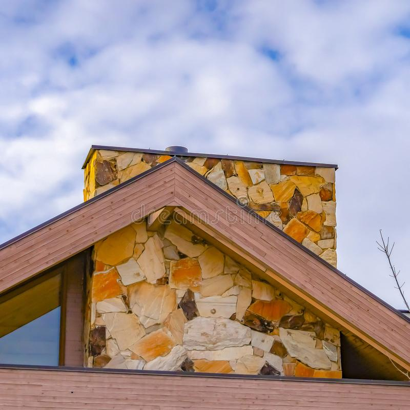Vierkante kader Dichte omhooggaand van het dak van een huis tegen bomen en hemel met donzige wolken stock afbeeldingen