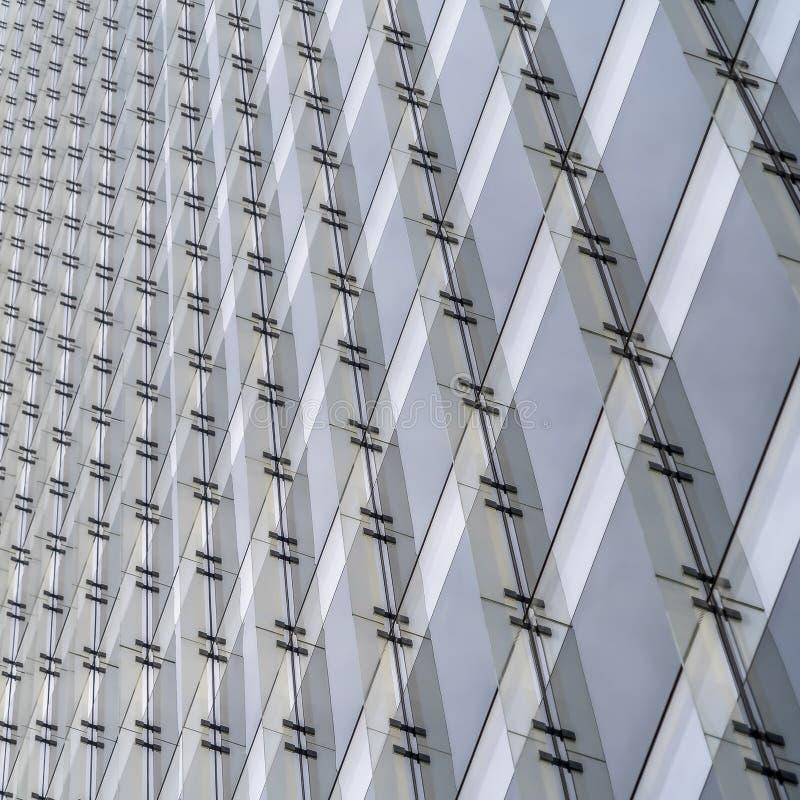 Vierkante kader Dichte omhooggaande mening van buitenkant van een gebouw met meerdere verdiepingen tegen heldere witte hemel royalty-vrije stock afbeeldingen