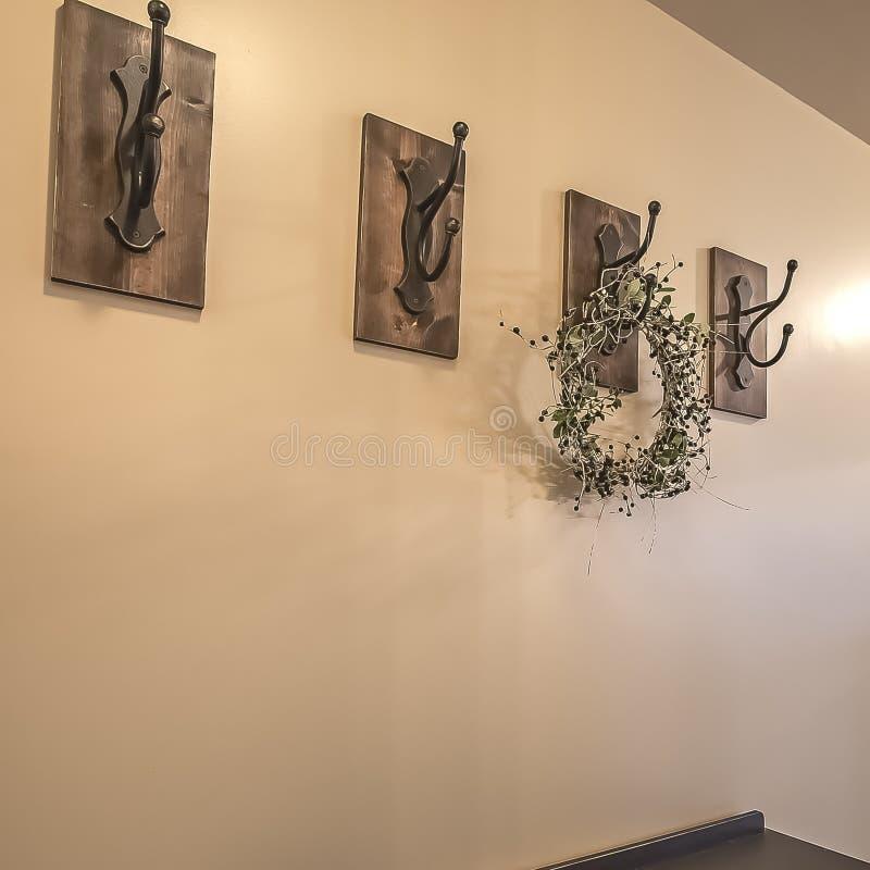 Vierkante kader Houten kabinetten en ijzerhaken tegen de beige muur van een huis met witte vloer stock afbeeldingen