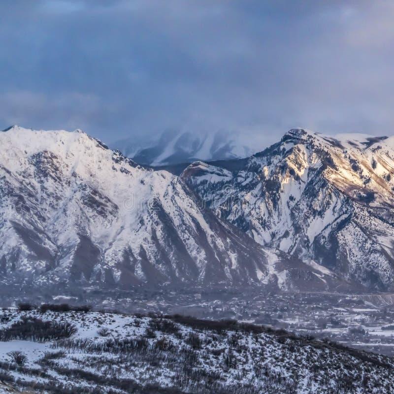 Vierkante kader Majestueuze die berg met sneeuw onder blauwe hemel met grijze gezwollen wolken wordt behandeld royalty-vrije stock foto's