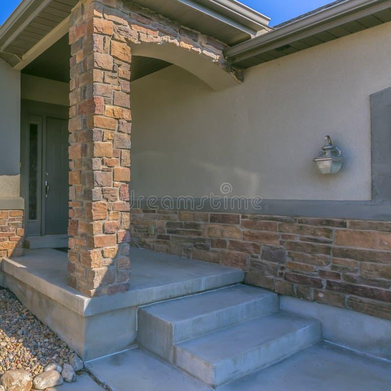 Vierkante kadervoorgevel van een huis met een rotsachtige yard en een kleine voorportiek royalty-vrije stock foto