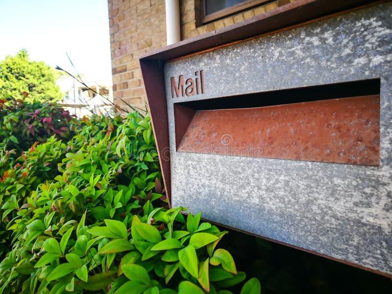 Vierkante metaalbrievenbus bij voor een gebouw met groentuin royalty-vrije stock fotografie