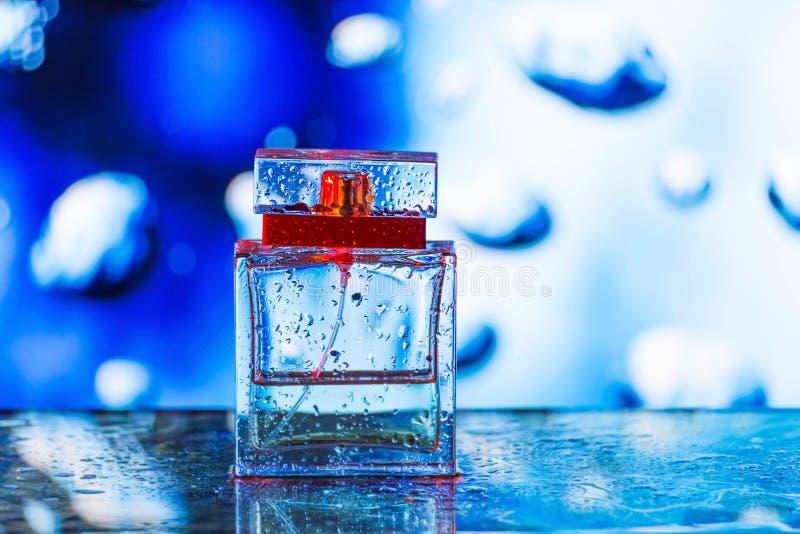 Vierkante parfumfles op blauwe, witte en rode achtergrond royalty-vrije stock afbeeldingen