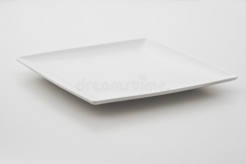 Vierkante porseleinplaat op witte achtergrond bij hoek stock foto