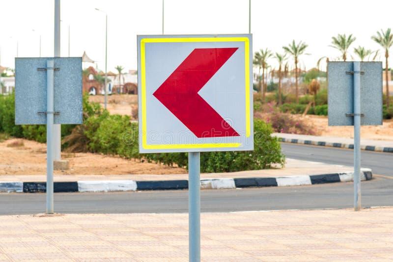 Vierkante witte verkeersteken met een rode die pijl aan de linkerzijde wordt gedraaid Horizontaal kader royalty-vrije stock fotografie