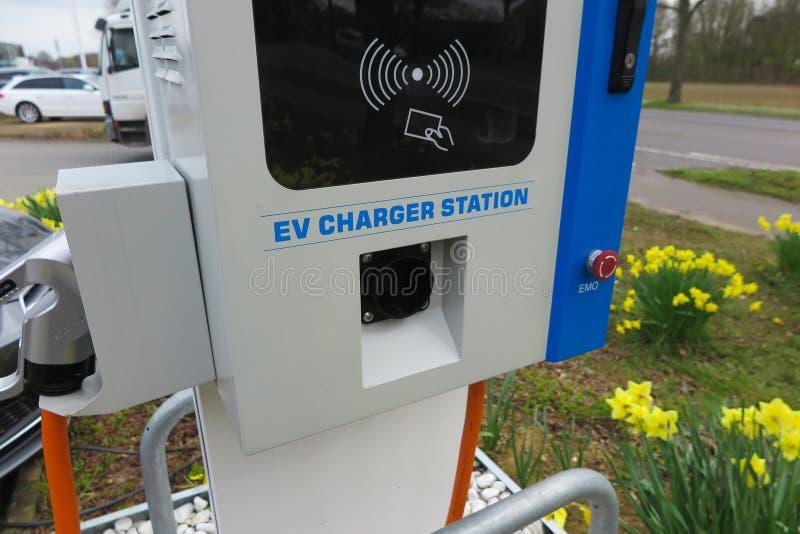 VIERSEN, ГЕРМАНИЯ - 27-ОЕ МАРТА 2019: Закройте вверх зарядной станции для электрических автомобилей окруженных желтыми тюльпанами стоковое изображение rf