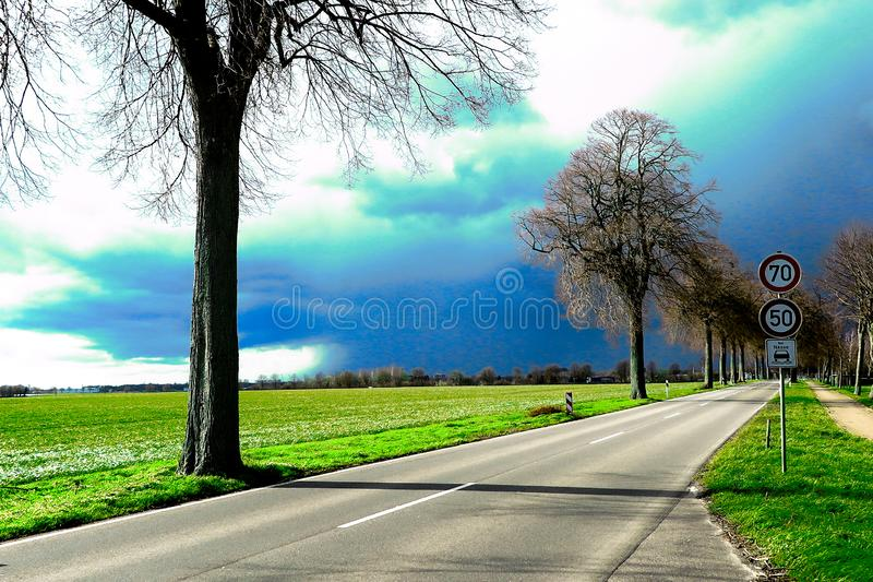 VIERSEN, ALEMANHA - céu escuro com a saraiva que carrega nuvens sobre a estrada secundária e as árvores desencapadas que anunciam fotografia de stock