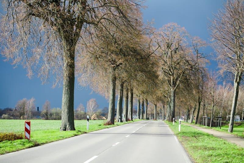 VIERSEN, ALEMANHA - céu escuro com a saraiva que carrega nuvens sobre a estrada secundária e as árvores desencapadas que anunciam imagens de stock royalty free