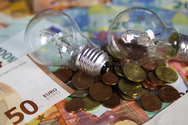 VIERSEN, ALEMANHA - 20 DE MAIO 2019: Conceito do custo da fonte de alimentação - ampolas elétricas em cédulas do papel moeda do E fotos de stock royalty free