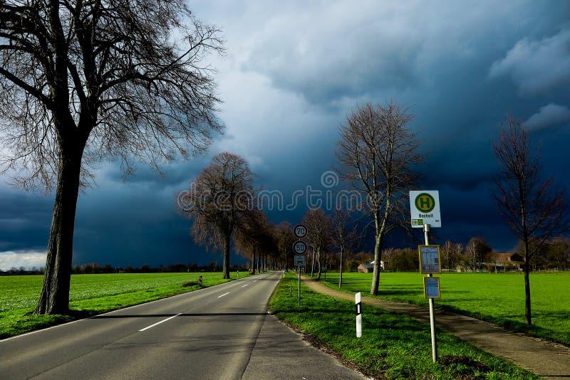 VIERSEN, DEUTSCHLAND - bewölkter Himmel mit dem Hagel, welche Wolken über der Landstraße und bloße Bäume ankündigen Gewitter träg stockfoto