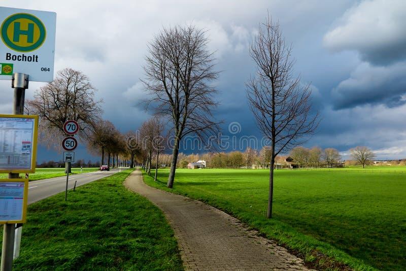 VIERSEN, DEUTSCHLAND - bewölkter Himmel mit dem Hagel, welche Wolken über der Landstraße und bloße Bäume ankündigen Gewitter träg lizenzfreie stockbilder