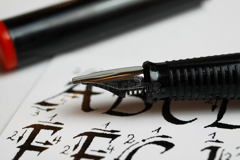 Handwriting and calligraphy learning concept: Macro closeup of ink pen and calligraphic handwritten alphabet letters. Viersen, Germany - April 30. 2020 royalty free stock image