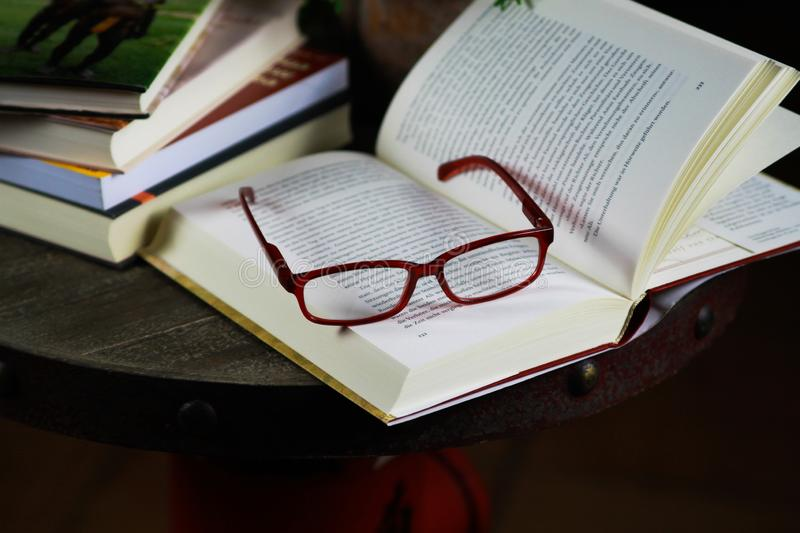 View on open book with red reading glasses and stack of travel books royalty free stock images