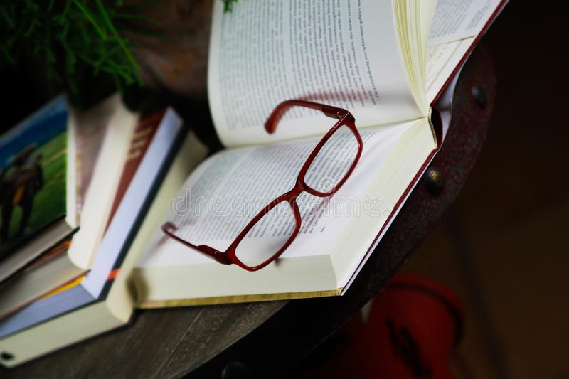 View on open book with red reading glasses and stack of travel books stock photo